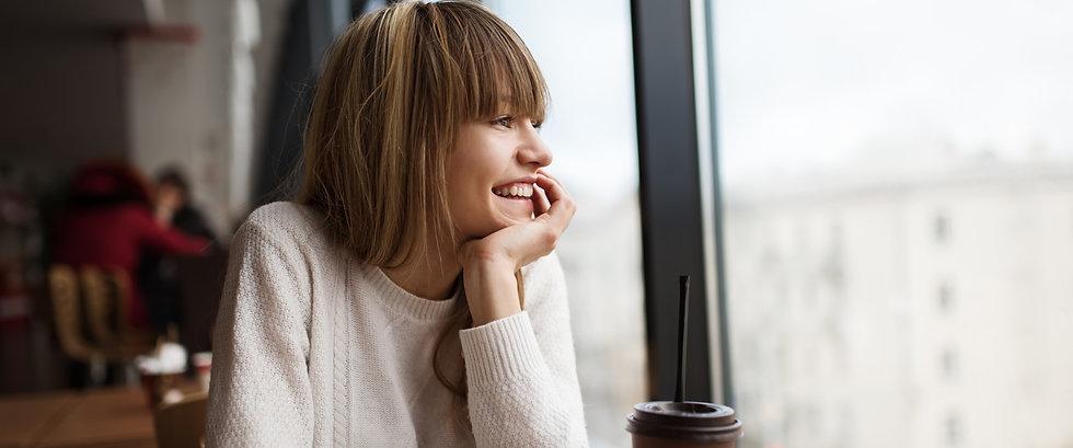 Female customer in white sweater enjoying indoors at Coffee Ta Cream