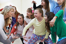 A group of elementary kids having a blast are seen reacting to a teacher who is engaging them in an after school Drama Lab acting activity.