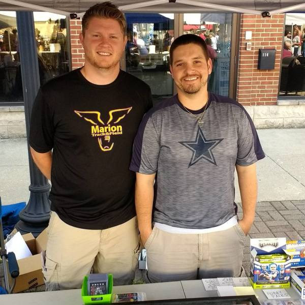 Jonathan Keith & Andrew Dicken standing at their booth at a sports card event