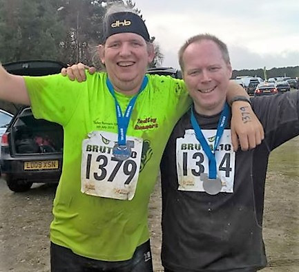 Paul (in muddy yellow) triumphantly finishes the Brutal 10k with his mate John earlier this year