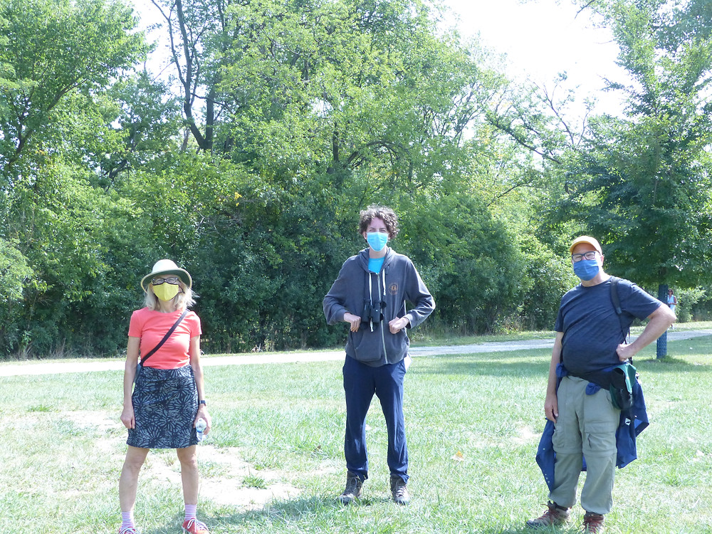 THree social distanced and masked people. Thomas is tall with curly hair.