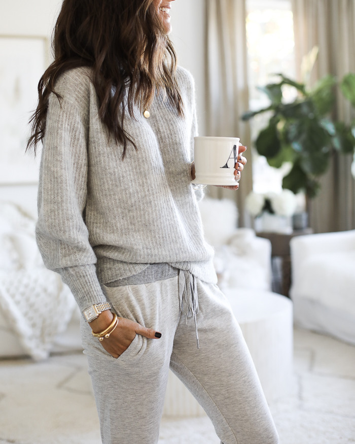 A woman smiling in living room holding a coffee mug wearing gold jewellery and a greay sweatshirt with grey sweat pants