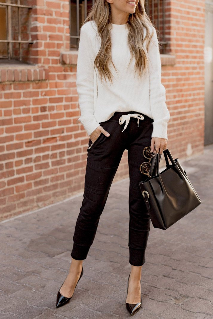 A blonde woman standing in front of red brick wall wearing black joggers with white cashmere sweater holding a black leather bag with matching black heels