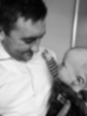 man with baby, chiropractor treating baby, baby looking at chiropractor, happy baby being treated