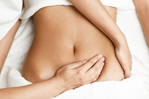 Top view of hands massaging female abdom