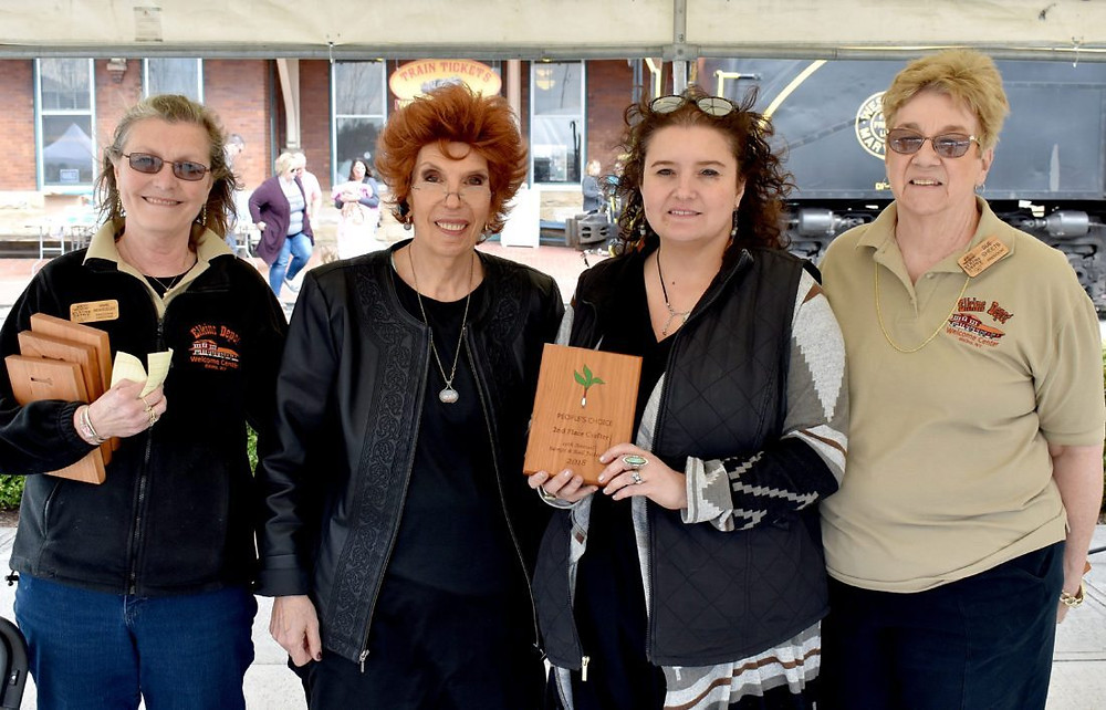 The tie for second place of the craft vendor portion of the 2018 Ramps and Rail Festival includes Denise Heckel of Studio D Pottery in Elkins, second from right, and Kate Searfoss of Lloyd Creations of Elkins. The pair received their award from Elkins Depot Welcome Center Executive Director Anne Beardslee, left, and Elkins Depot Welcome Center President of the Board of Directors Sue Sheets, right.