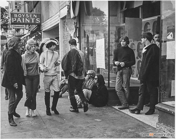 People walking on the sidewalk and sitting in front of storefronts on Haight St near Ashbury, circa 1967.