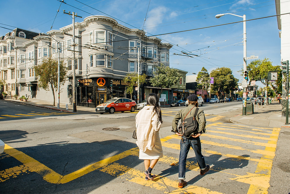 Couple walking in the crosswalk of the intersection of Haight and Ashbury streets.