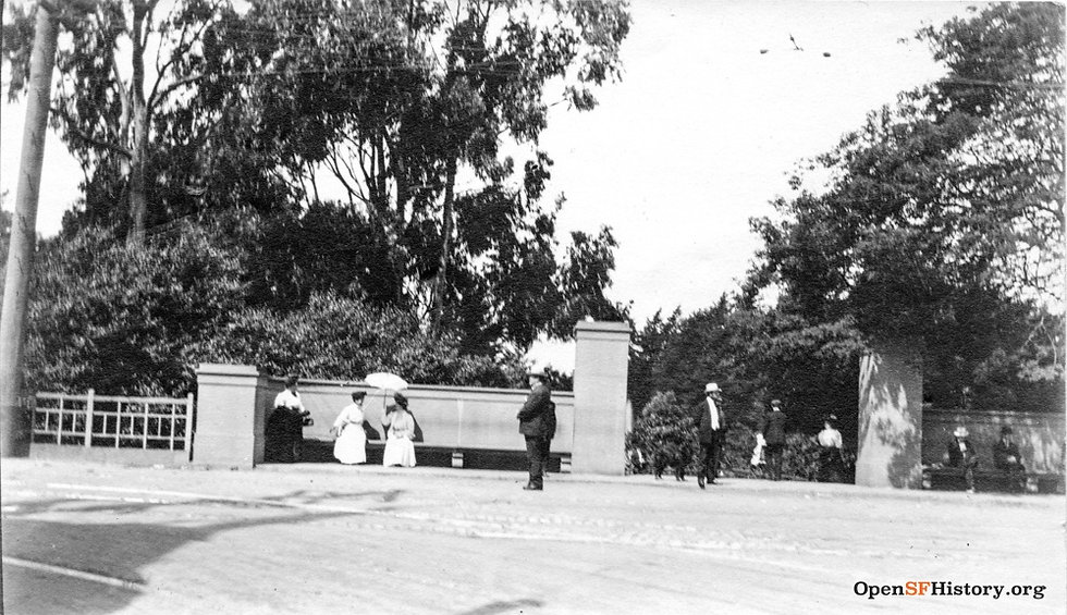 People gathering at a bench at the intersection of Stanyan at Haight on May 31, 1909. The womens are wearing long skirts and carrying parasols; the men are wearing hats.