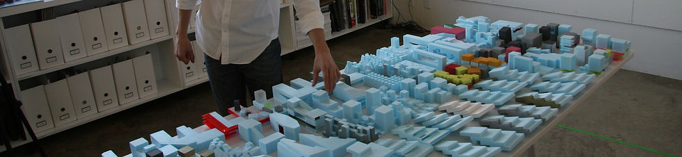 Hand adjusts an architectural model.