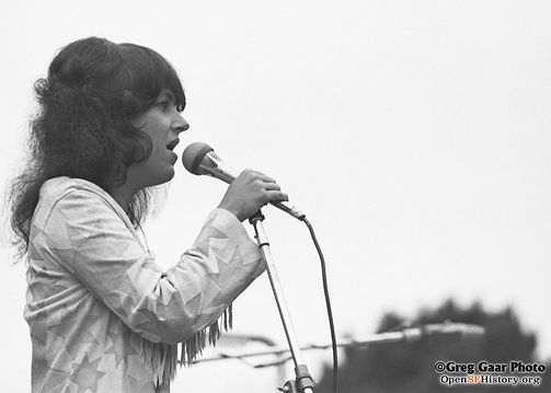 Grace Slick, singer of Jefferson Airplane, singing into a microphone.