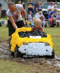 WE ALL GET BY WITH A LITTLE HELP FROM OUR FRIENDS… Samuel Roland gets a push from Billy Losh-bough after his car bogged down during the Power Wheels Division of the Saturday after-noon's Mudd Run. (TCR photo by Kristy Noack)