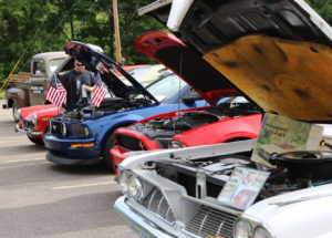 SUN'S OUT; HOODS UP… With the hoods up on a line of classic cars including two Ford Mustangs and a Pontiac Bonne-ville, Nate Wolfe of South Ha-ven checks out the engines dur-ing Saturday's car show honor-ing veterans at Arclight Bre-wery. (TCR photo by Kristy Noack)