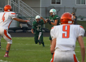 HOT HANDOFF… Hartford quarterback Evan Parker pre-pares to hand off the football to Robert Ledesma Jr. Friday evening. Hartford scored their first TD of the season, but lost 57-7 to Gobles, at home. (TCR photo by Kristy Noack)