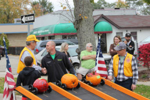 COLOMA LION'S PUMPKIN RACERS… Doug Kraemer (center) shakes the hands of Shane Kreitner and John Whist-ler as they get ready to race their pumpkins on Saturday. Ross Streu gets ready to send them flying as the crowd watches in the background. (TCR photo by Christina Geld-er)