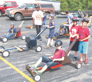 """Wabano Cubmobile… A gathering of more than 100 Tigers, Wolfs, Bears and Webelos on June 4 at Lane Automotive produced plenty of action and fun during the Wabano Cubmobile 2016 event. Wabano is a district within the Southern Shores Field Service Council which is part of the Boy Scouts of America Michigan Crossroads Council. Nathan Mashman, Unit Serving Executive for the Wabano District, said Scouts helped navigate fellow Scouts across the finish line in the one-seater Cubmobiles. He said they also had the opportunity to participate in a Rain Gutter Regatta; Gaga Pit; Sling Shot Game; STEM activities; and a Robotics Team. Members of the Coloma and Watervliet Fire and Emergency Medical Services department also got in on the action. """"This is a great way for our Scouts to get to know each other and participate in activities that are a part of what we do in Scouting to teach leadership and life skills,"""" Mashman said. """"The Cubmobile competition promotes teamwork which is a critical part of our ability to build youth who will be prepared to work through any challenges they are presented with. To learn more about the Scouting program in Michigan or to get involved, please contact Mashman at Nathan.mashman@ scouting.org or visit the MCC website at www.michiganscouting.org."""