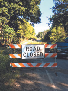 """LONG DETOUR… The """"Road Closed"""" sign remains on Territorial Road in Millburg and will likely re-main there until spring. Funding and DEQ demands along with permitting issues have delayed the work of the Berrien County Road Commission for this culvert that collapsed into the creek below in April. School bus routes, customers of the local busi-nesses, and local residents alike con-tinue to be affected by this detour. (TCR photo by Annette Christie)"""