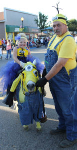 """BEST OVERALL… Lyla Current was assisted by her grand-father, Dan Atherton at the Co-loma Glad-Peach Youth Parade as they won Best Overall with their Minion theme. The pony also had a sign saying """"Life is a Peach in Coloma…there are a Minion things to make you Glad"""". Lyla's mother Rebecca says that Lyla picked the theme this year. (TCR photo by Christina Geld-er)"""
