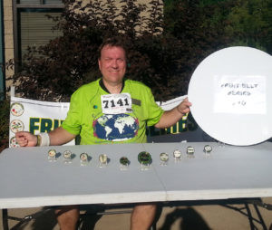 PERFECT 10… Martin Quigley Jr. of Coloma poses in front of his ten Fruit Belt Series medals after completing the Lawrence Watermelon 5k run on Satur-day. Quigley Jr., founder of the series, has raced in at least five qualifying Fruit Belt Series 5k events for the past 10 years and is the only participant to do so. (TCR photo by Kristy Noack)