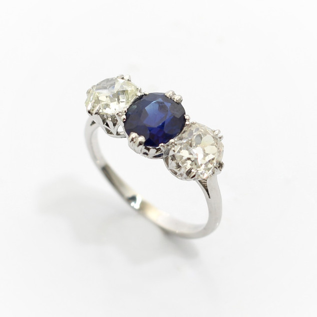 A platinum sapphire and diamond three stone ring. The central oval sapphire 1.65cts, with two old cut diamonds to either side at 0.85ct each. G colour, Vs2/ Si2 clarity. Completed in coronet claw settings. £12,000.00
