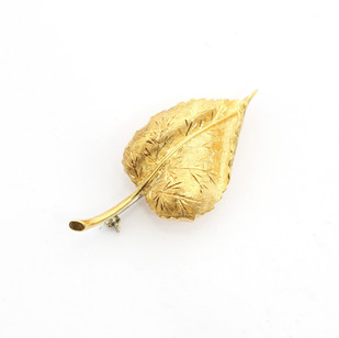 18ct yellow gold brooch in the form of a curled autumn leaf with fancy engraved vine decoration. £525.00