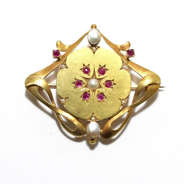 A 15ct yellow gold, ruby and half pearl Art Nouveau brooch. £475.00