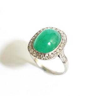 Platinum cabochon emerald and diamond cluster ring. The central emerald 5.63cts, with border of brilliant cut diamonds. Totalling 1.20cts. £5,000.00