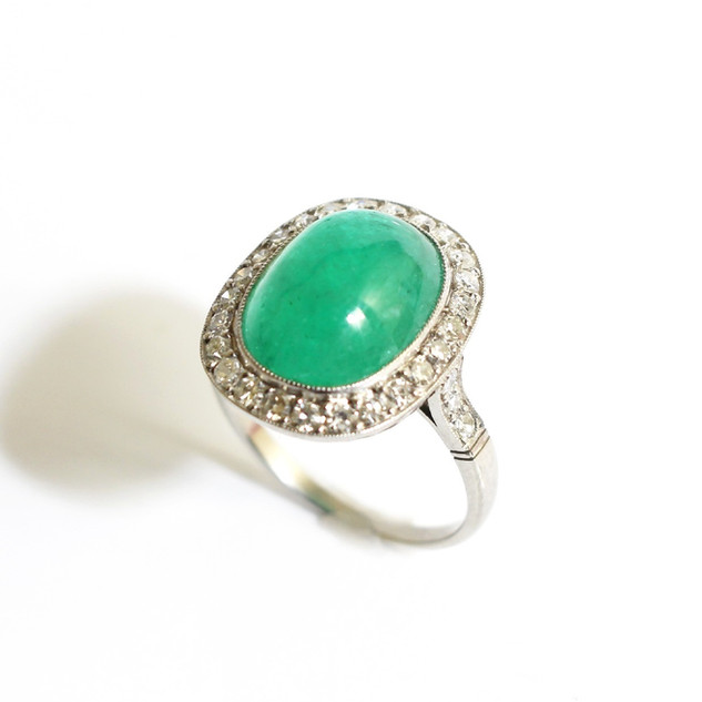 A platinum cabochon emerald and diamond cluster ring. The central emerald 5.63cts, with border of brilliant cut diamonds totalling 1.20cts. £5,250.00