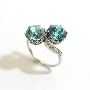 A platinum and zircon cross over ring with diamond set mount. The exceptional blue zircons 8.15cts each. £5,250.00