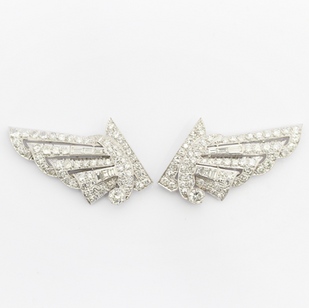 A platinum and diamond double clip brooch. To be worn as clips or together with fittings as a complete brooch. Each panel comprising of old cut, eight cut and tapering baguette cut diamonds. Estimated total weight 8cts.  In original fitted case. 15th St Andrews Ball, Grosvenor House, December 1935.