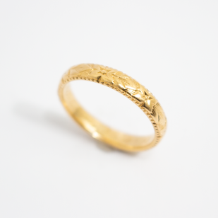 18ct yellow gold wedding ring with fancy floral engraved centre, completed with fine millgrain edge above and below. Hallmarked 1907, finger size M.