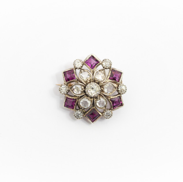 18ct yellow gold mounted and silver fronted garnet and diamond, late Victorian brooch / pendant. Comprising of a circular old cut diamond at centre of six rose cut diamonds in a floral bud design. Six outer almandine garnets alternating with six smaller circular old cut diamonds. Removable brooch fitting with provision for wear as pendant. Circa 1890. £2,650.00