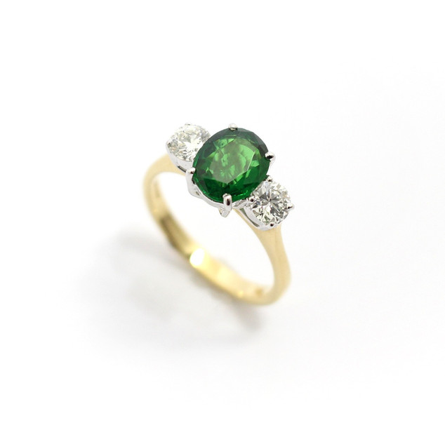 18ct yellow and white gold mounted Tsavorite garnet and diamond three stone ring. The central very fine coloured green garnet oval shaped 2.11cts. Set with two circular modern brilliant cut diamonds, 0.25ct each, G colour, Vs clarity. In claw settings. £5,250.00