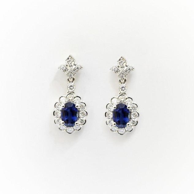 18ct white gold sapphire and diamond cluster drop earrings. The oval sapphires totalling 1.30cts with surrounds of brilliant cut diamonds and a diamond fleur-de-lis drop feature. Diamond weight 0.61ct. £3,500.00