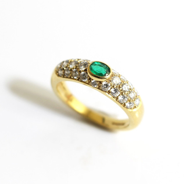 18ct yellow gold emerald and diamond ring. The central oval emerald 0.17ct, with a diamond set band totalling 0.67ct, G colour, Vs clarity. £2,250.00