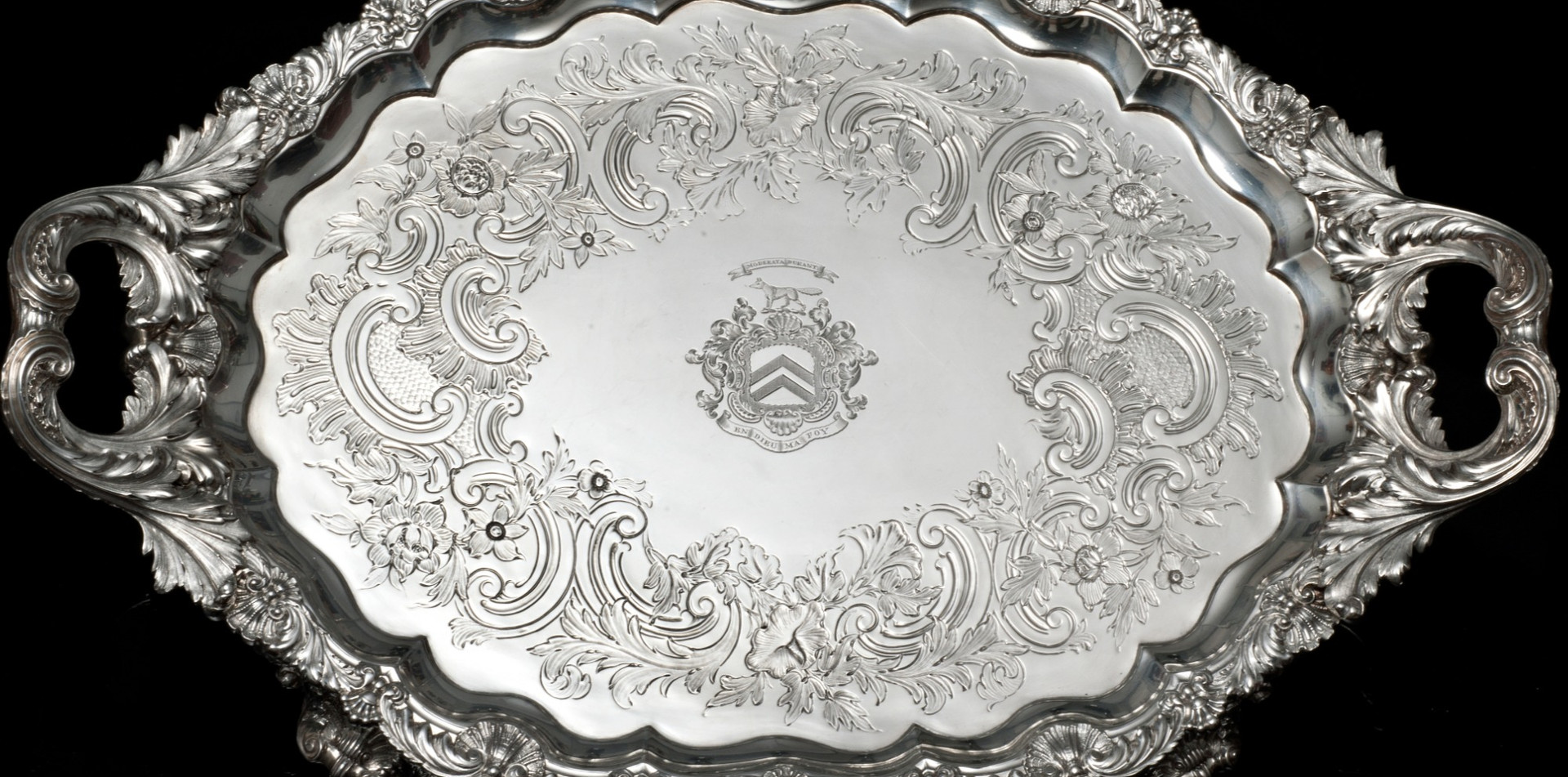 "Regency Tray by Paul Storr   Oval Two Handled Silver Tray Shell and foliage scroll border and handles.  Shell and grape feet. Contemporary flat chasing.   ""The exuberance of the feet and handles are a feature of Paul Storrs regency work.""   1818 112 oz 22 inches over handles Engraved with Staunton arms (running fox) and mottos: Moderata Durant - Moderate things are permeant En Dieu Est Ma Foy – On God is my Reliance £22,500.00"