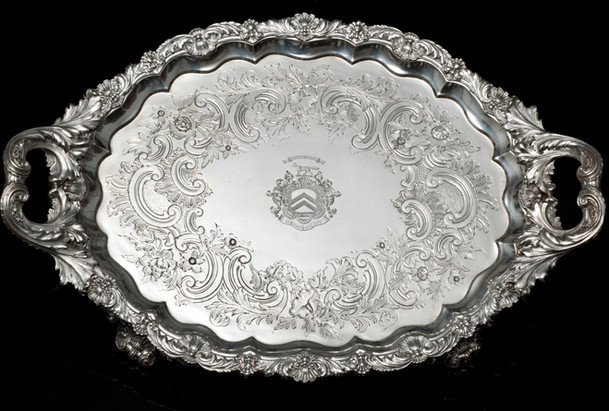 """Regency Tray by Paul Storr   Oval Two Handled Silver Tray Shell and foliage scroll border and handles.  Shell and grape feet. Contemporary flat chasing.   """"The exuberance of the feet and handles are a feature of Paul Storrs regency work.""""   1818 112 oz 22 inches over handles Engraved with Staunton arms (running fox) and mottos: Moderata Durant - Moderate things are permeant En Dieu Est Ma Foy – On God is my Reliance £22,500.00"""