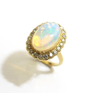 18ct yellow gold opal and diamond cluster ring. The central opal 9cts with millgrain set border of diamonds totalling 0.60ct. £3,250.00