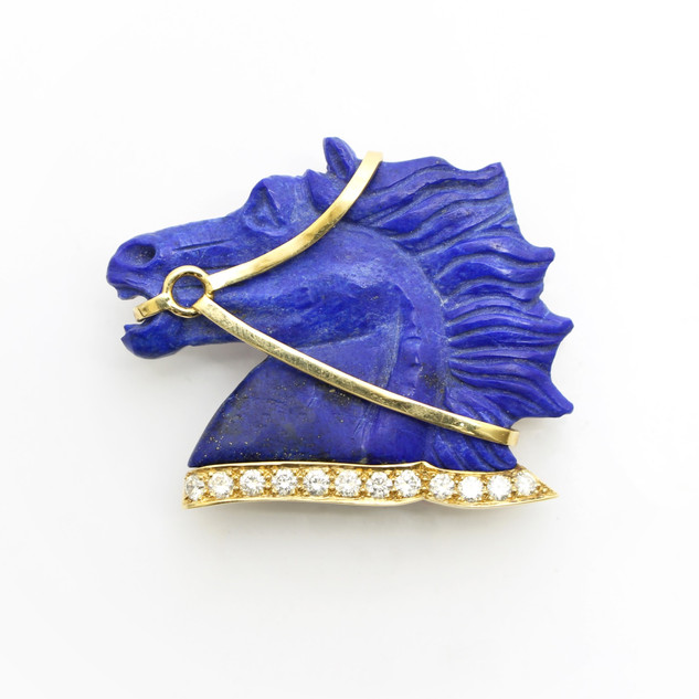 A hand carved lapis and 18ct yellow gold horse head brooch. Set with a modern brilliant cut diamonds. The diamonds weighing 0.60ct, G colour, Vs1 clarity. In a handmade setting. £3,750.00