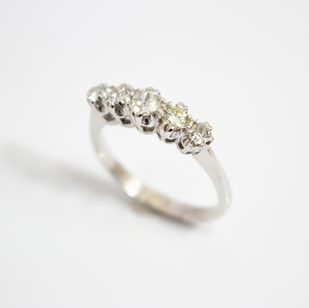 18ct white gold diamond five stone half hoop ring. The five graduated old cut diamonds totalling approximately 0.56ct, slightly tinted in colour, pique clarity, coronet claw setting. £1,250.00