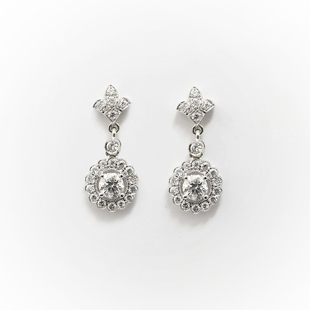 18ct white gold diamond cluster drop earrings. Each earrings comprising of a central brilliant cut diamond at 0.21ct each and completed with a surround of brilliant cut diamonds below a diamond fleur-de-lis feature. Total diamond weight 1ct. £3,900.00