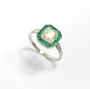A platinum cushion cut solitaire diamond ring with a border of calibre cut emeralds and diamond set shoulders. The central cushion cut diamond 1.16ct, Slightly tinted, Vs clarity. £7,500.00