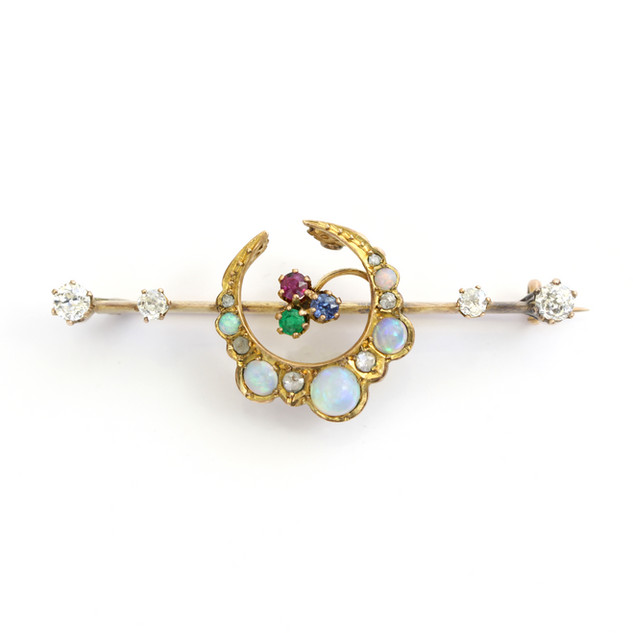 15ct yellow gold bar brooch/ Comprising of a central opal set open crescent brooch with gem set centre, completed with diamond points. £1,200.00