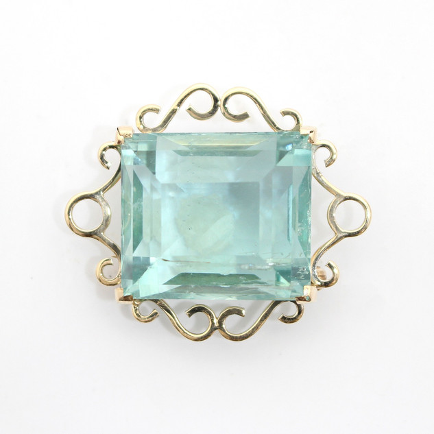 14ct yellow gold aquamarine brooch. Comprising of a large step cut aquamarine of almost green colour, estimate 33cts. Fancy gold wire work frame surround. French, Circa 1940. £2,650.00