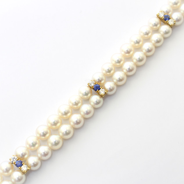 A two row cultured pearl bracelet, the well matched fine quality white pearls completed with three 18ct yellow gold mounted spacing bars set with sapphires and diamonds. Completed with 18ct gold clasp. £2,250.00