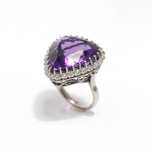 A large amethyst dress ring. The impressive amethyst approximately 22cts. Set within a border of diamonds and completed with a decorative white gold scroll setting. £1,850.00