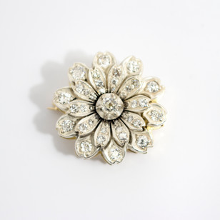 18ct yellow gold mounted and silver fronted late Victorian flower bloom brooch. Comprising of a central old cut diamond within a claw setting with diamond set petals. Circa 1880. £3,250.00
