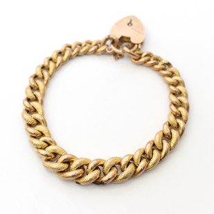 9ct yellow gold curb link bracelet. The graduated curb links with fancy engraved decoration. Completed with heart padlock. £450.00