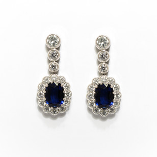 18ct white gold sapphire and diamond cluster drop earrings. The oval mixed cut sapphires 1.98cts each with a surround of circular brilliant cut diamonds and trio of brilliant cut diamond drops. Diamond weight 2.98cts. £16,000.00