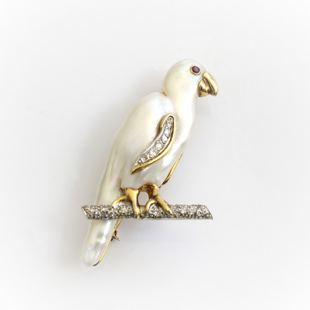 18ct gold mounted 'Parrot' brooch. The parrots body formed by a single large baroque pearl, completed with gold beak, ruby eye and diamond set wing, with diamond branch. £4,750.00
